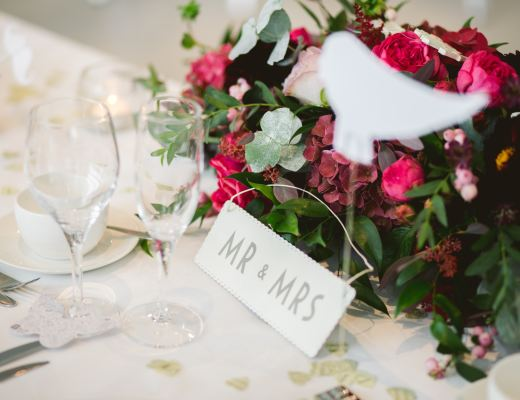 wedding table set up - bridal bouquet, wine glasses and a his and hers name card
