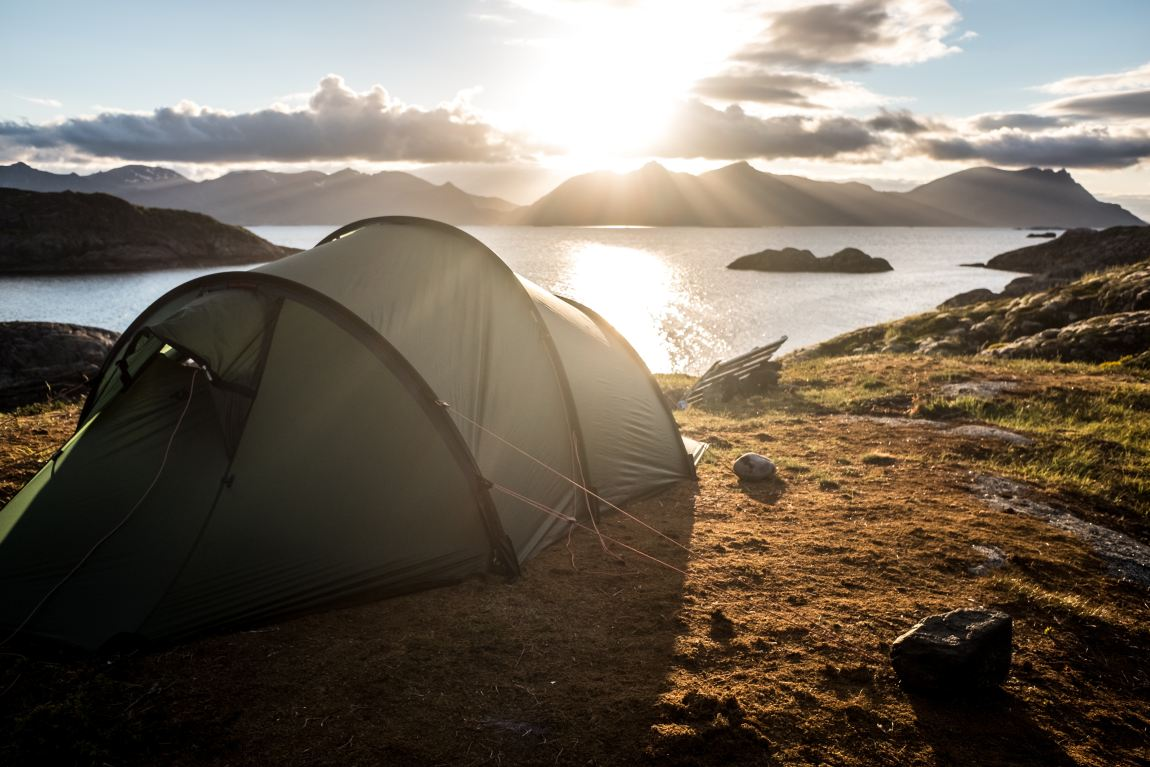 a tent overlooking a lake and mountains