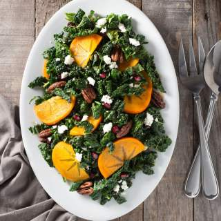Overhead shot of a platter of kale salad with pomegranates, persimmons, maple butter pecans and feta cheese.