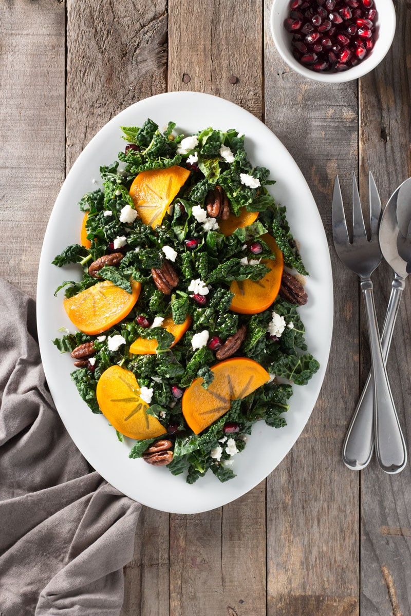 Overhead shot of a platter of kale salad with pomegranates, persimmons, maple butter pecans and feta cheese on a grey wood surface surrounded by utensils, a dish towel and a bowl of pomegranate seeds.