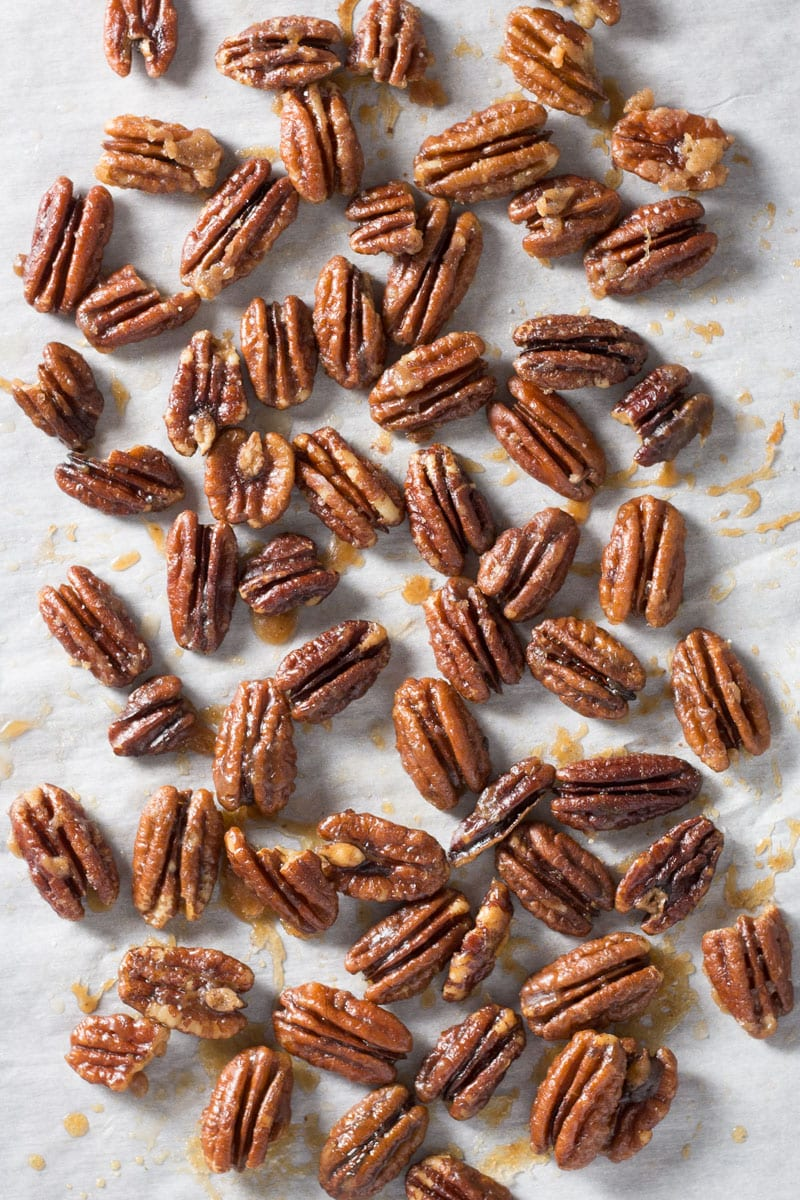 Overhead shot of Maple Butter Pecans spread out on parchment paper.
