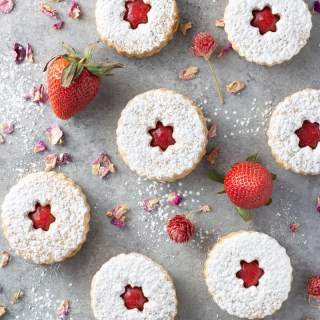 Overhead shot of linzer cookies dusted with powdered sugar and filled with strawberry rose jam, surrounded by fresh strawberries and dried rose petals on a light grey textured surface.