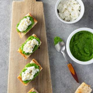 Overhead shot of crostini topped with ramp pesto and ricotta cheese on a light wood cutting board, surrounded by bowls of ricotta and ramp pesto, a spoon and slices of toast on a grey, textured surface.