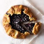 Overhead shot of a lavender blueberry galette on parchment paper on a light, textured background.