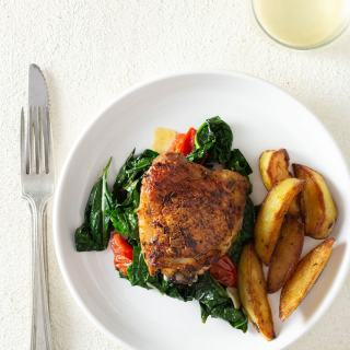Overhead shot of a crispy lemon pepper chicken thigh over sauteed kale, garlic and tomatoes, next to crispy potato wedges on a white plate surrounded by a glass, a fork and a knife on a white, textured plaster surface.