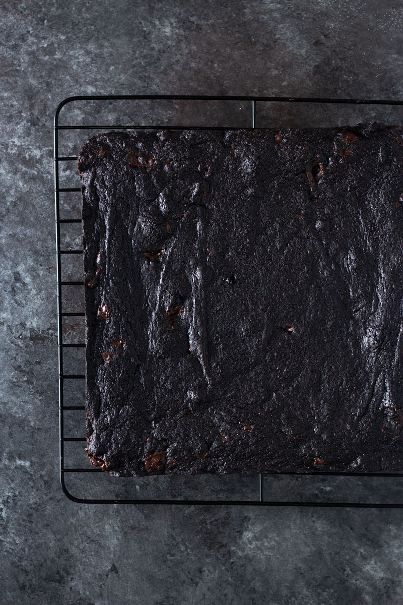 Overhead shot of dark chocolate chunk brownies on a cooling rack on a dark, rustic textured background.