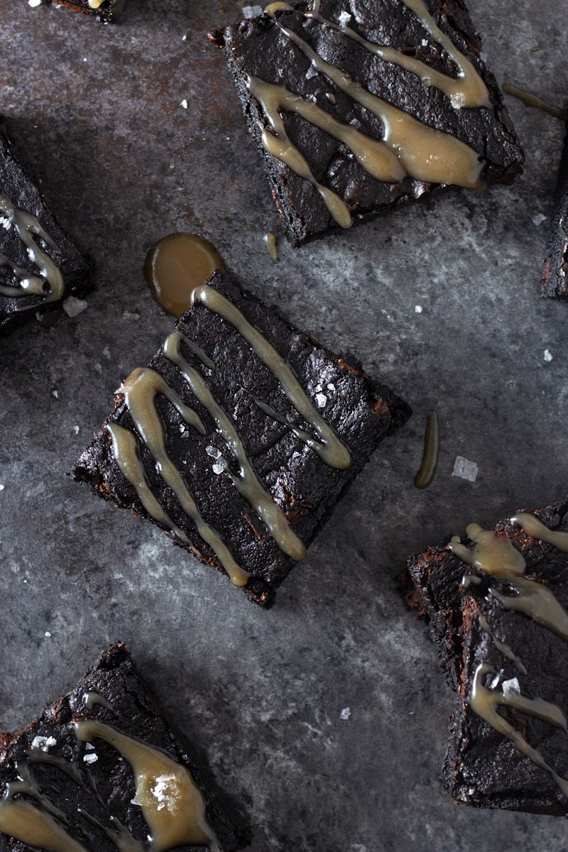 Overhead shot of dark chocolate chunk brownies drizzled with tamarind salted caramel and topped with maldon salt on a dark, rustic textured background.