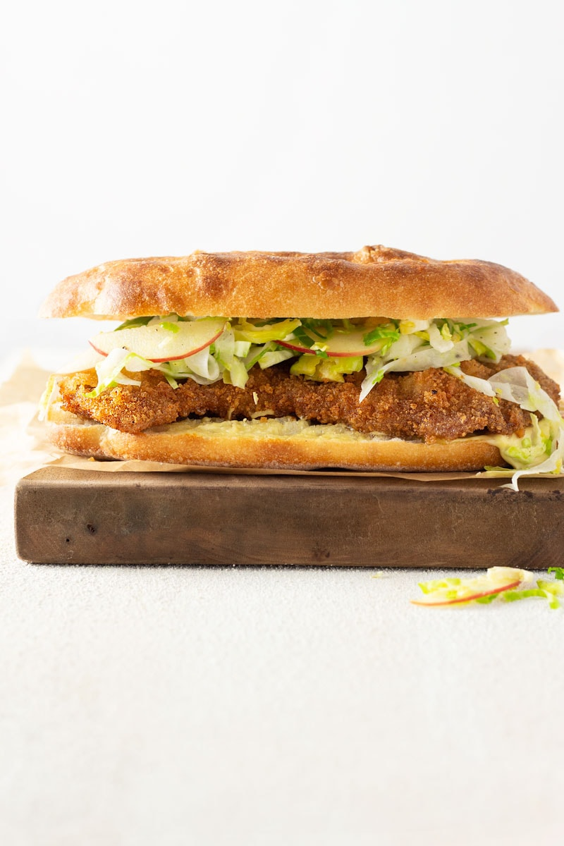 Straight on shot of a Pork Schnitzel Sandwich with Apple Brussels Sprout Slaw on a mini focaccia bread on parchment paper on a wooden cutting board on a white plaster surface with a white background.