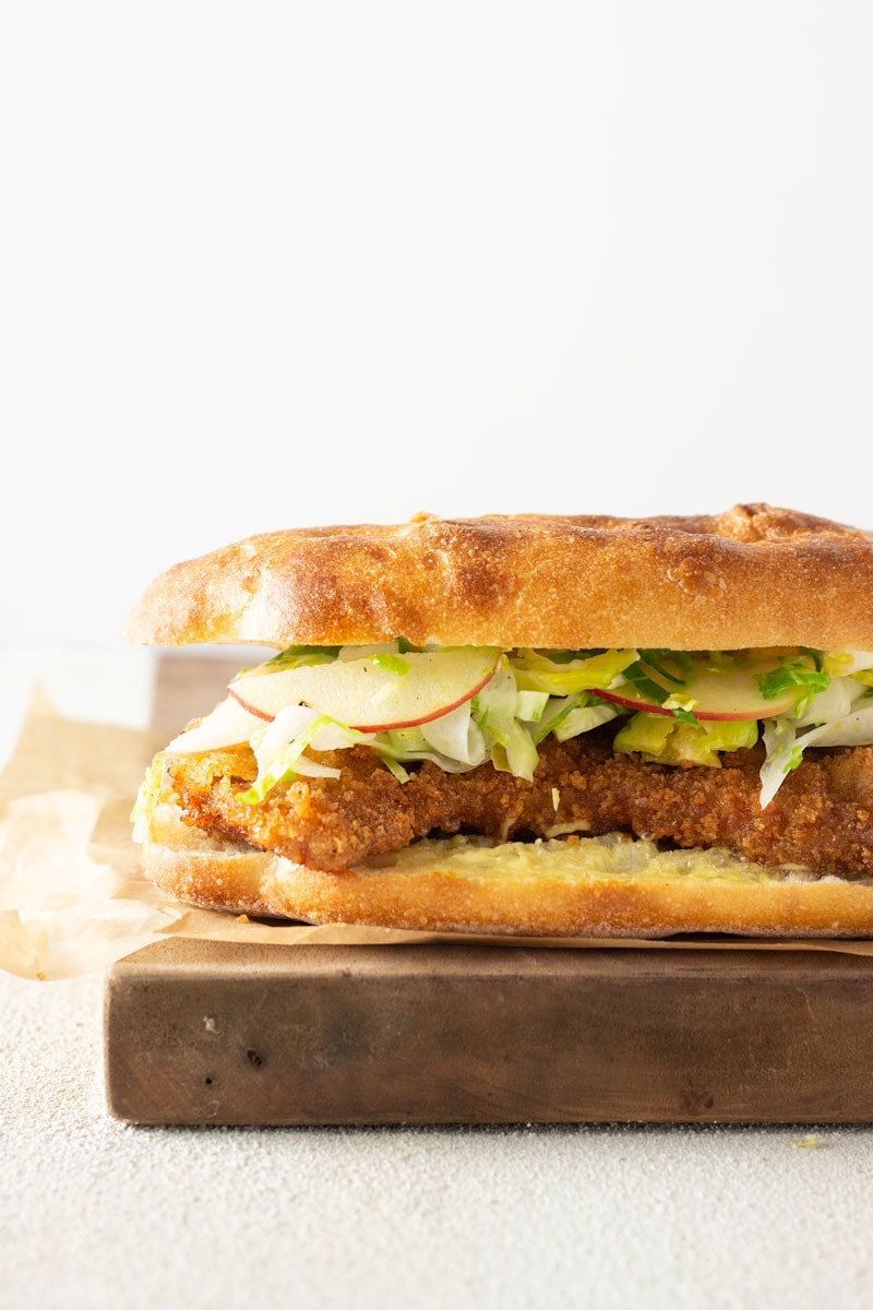 Straight on shot of a Pork Schnitzel Sandwich with Apple Brussels Sprout Slaw on a mini focaccia bread on parchment paper on a wooden cutting on a white plaster surface with a white background.