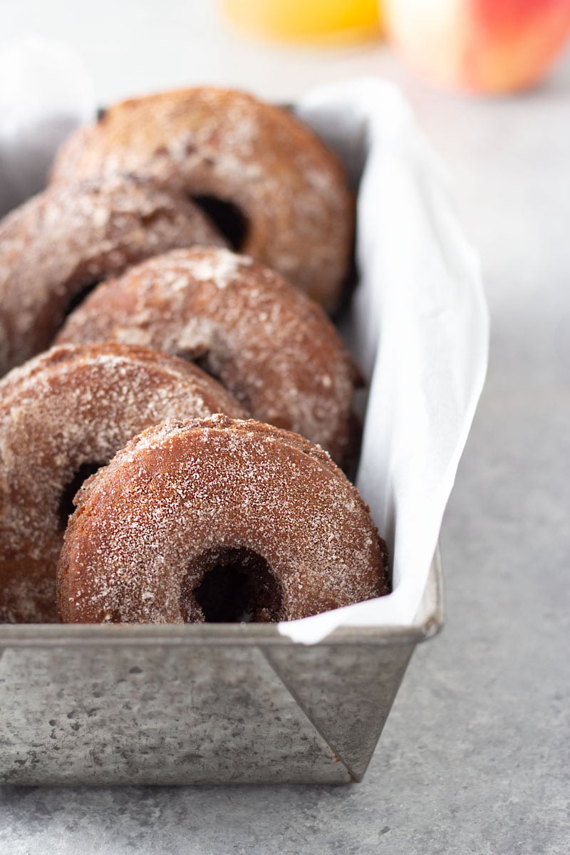 3/4 angled view of Apple Cider Donuts with Cinnamon Sugar in a metal baking tin with parchment on a light grey, textured surface with a glass of apple cider and an apple in the background.