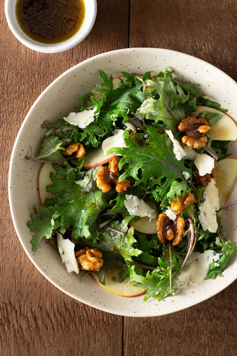 Overhead shot of a bowl of Kale and Apple Salad with Blue Cheese, Maple Glazed Walnuts and balsamic dressing on a dark wood surface surrounded by a small bowl of dressing.