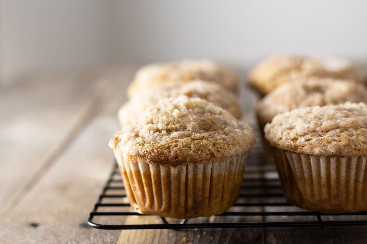 Straight on shot of a rack of Pumpkin Cream Cheese Streusel Muffins on a grey wood surface with a light background.