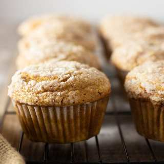 Straight on shot of a rack of Pumpkin Cream Cheese Streusel Muffins on a grey wood surface surrounded by a tan cloth with a light background.