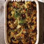 Overhead view of hands in a white sweater holding a red baking tray of Sausage Chestnut Stuffing topped with fresh thyme on a grey wood surface.