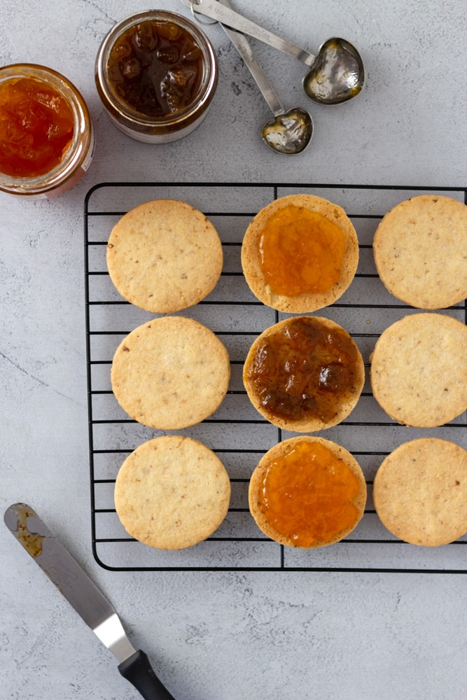 Overhead shot of hazelnut cookies on a cooling rack being filled with apricot and fig jams surrounded by jars of jam, measuring spoons and an offset spatula on a light blue grey surface.