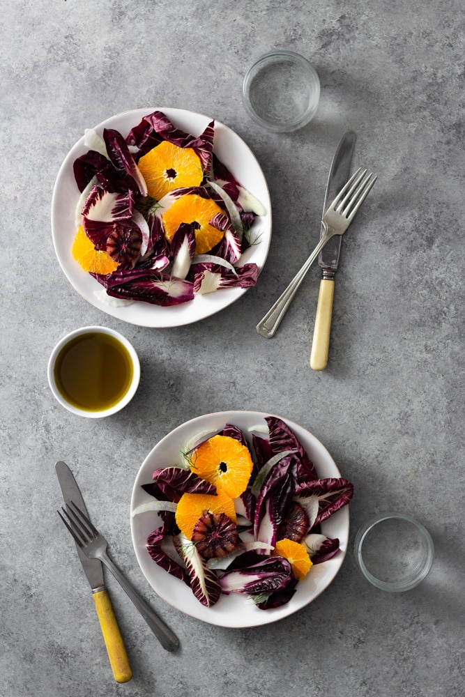 Overhead view of two plates of Orange and Fennel Salad with Radicchio, blood orange and fennel fronds surrounded by glasses of water, forks, knives, and a small bowl of dressing on a light grey, textured surface.