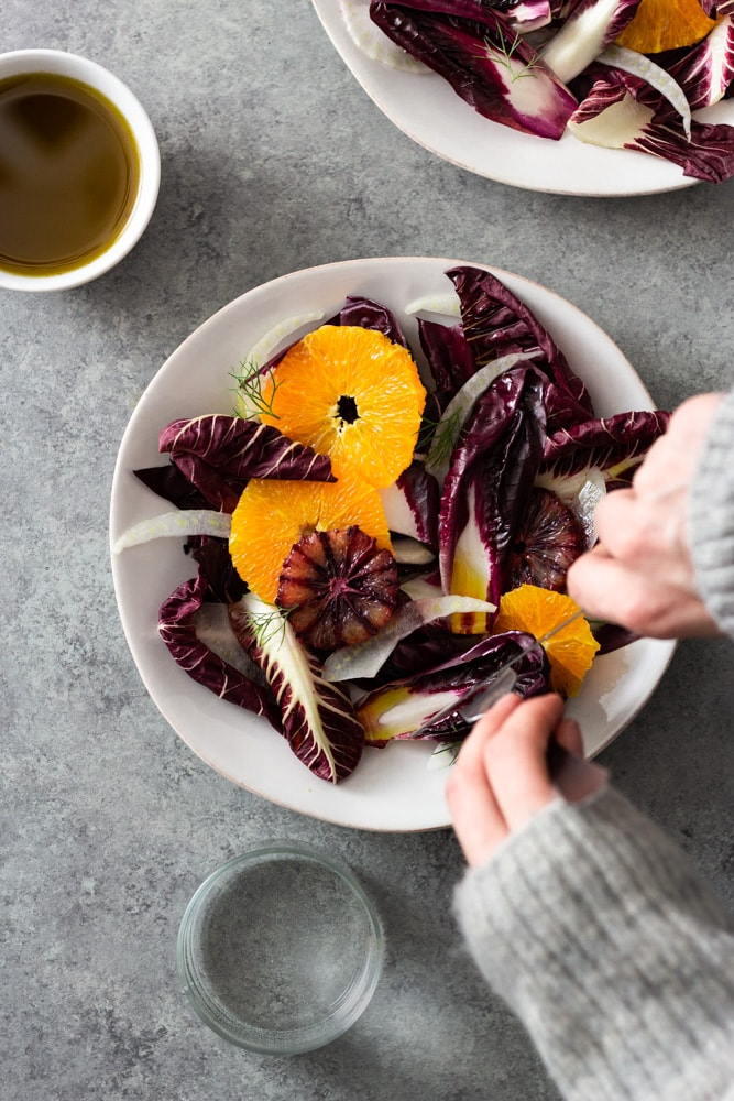 Overhead view of hands cutting into an orange and fennel salad with radicchio, blood orange and fennel fronds next to another bowl of salad, a small bowl of sherry vinaigrette and a glass of water on a light grey textured surface.