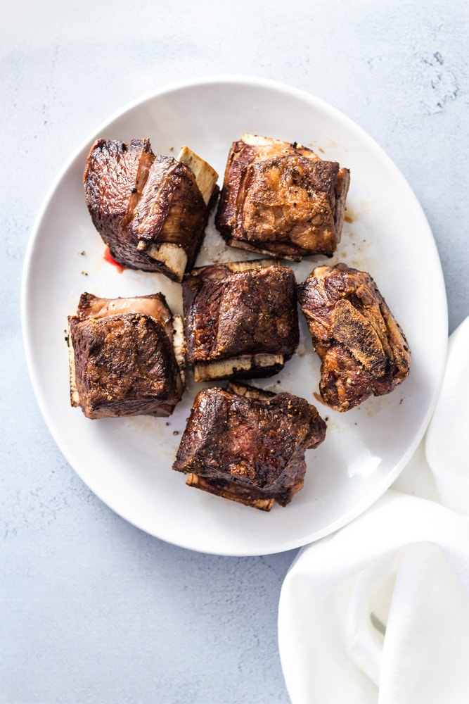 Overhead shot of a white plate with browned beef short ribs next to a white linen napkin on a light blue surface.