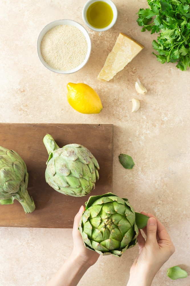 Overhead shot of prep for Italian Stuffed Artichokes. There is parsley, a bowl of olive oil, a bowl of breadcrumbs, a lemon, garlic, a dark wooden cutting board with fresh globe artichokes and hands peeling leaves off an artichoke a beige textured surface.