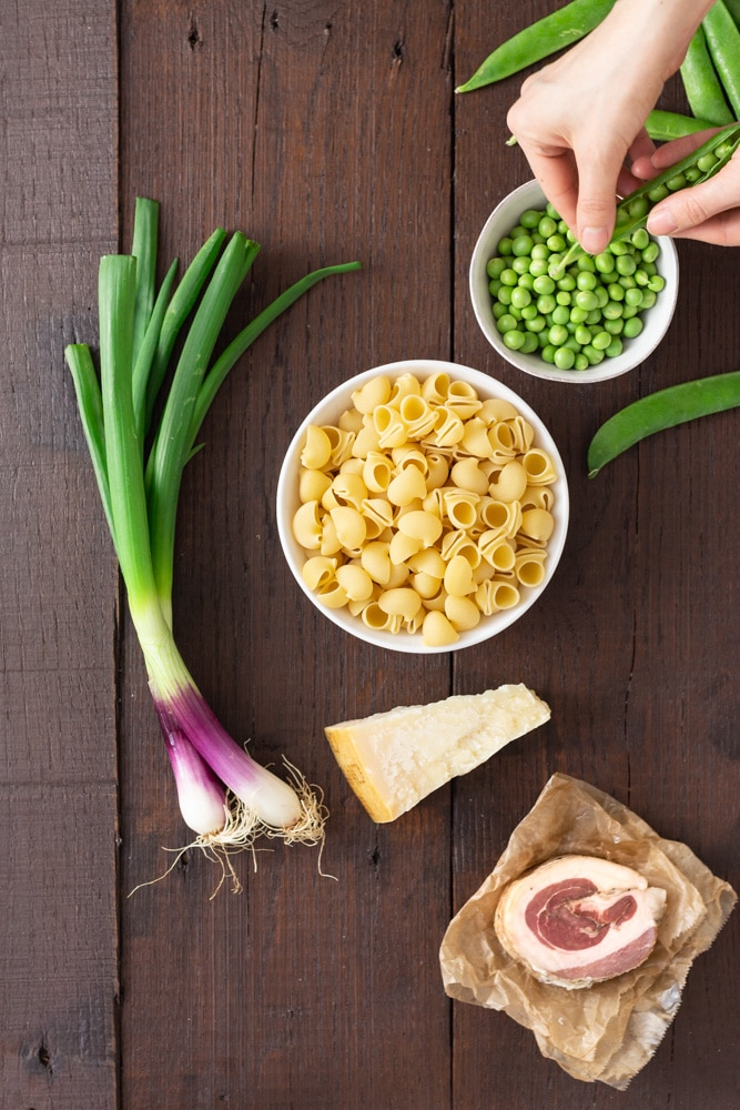 Overhead view of prep for pasta with peas and pancetta, including shell pasta, spring onions, pancetta, parmesan cheese and fresh peas on a dark wood surface.