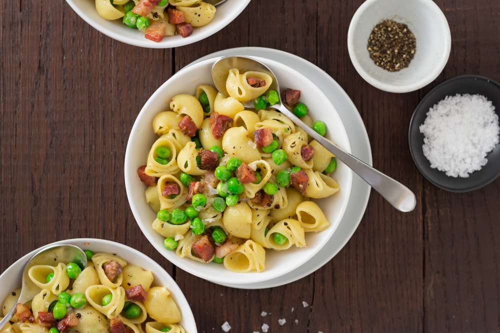 Overhead view of three bowls of shell pasta with peas and pancetta with spoons and small bowls of salt and pepper on a dark wood surface.