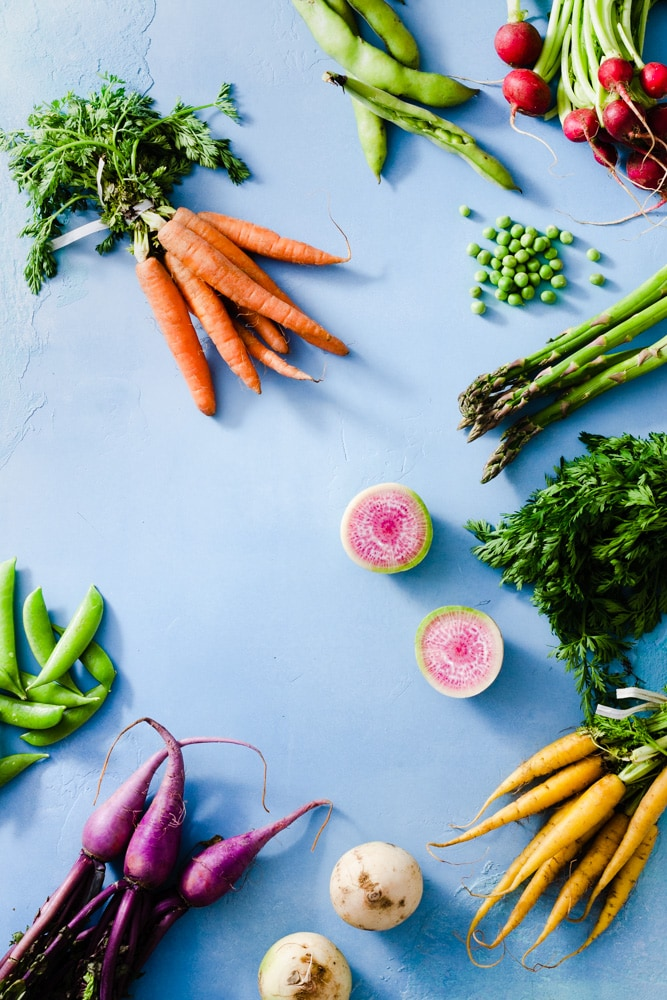 Overhead view of ingredients for a spring vegetable salad including snap peas, English peas, fava beans, red radishes, purple radishes, watermelon radishes, orange and yellow baby carrots and asparagus on a light blue background.