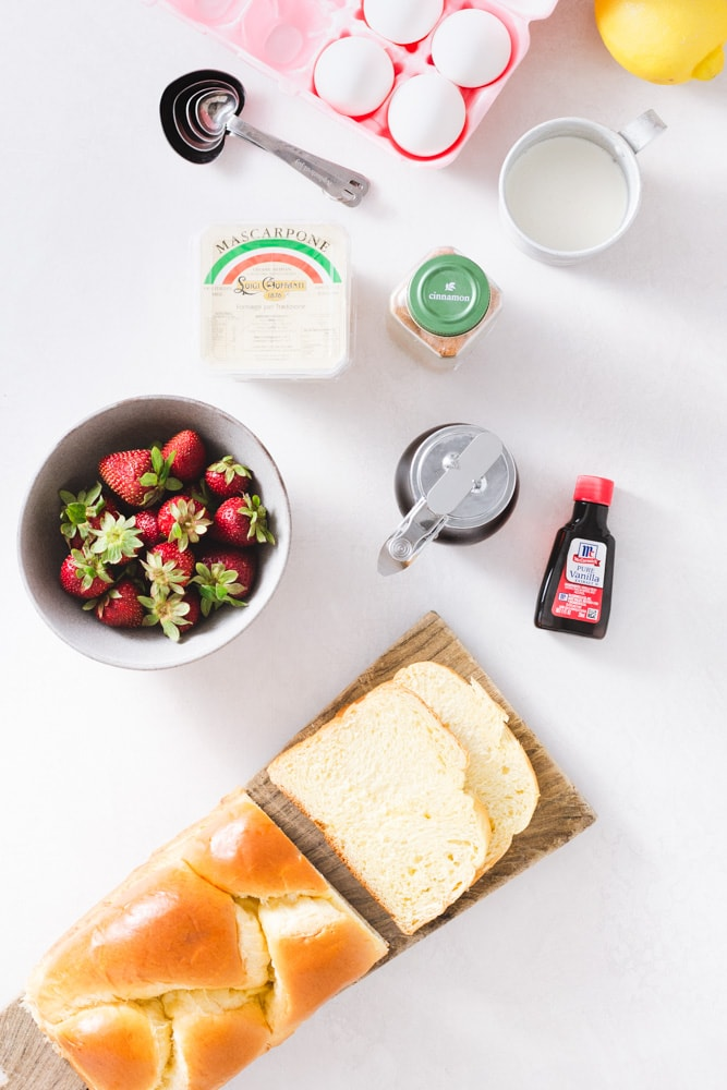 Overhead view of ingredients for French toast, including eggs, a lemon, cinnamon, maple syrup, vanilla extract, brioche bread, strawberries and mascarpone cream.