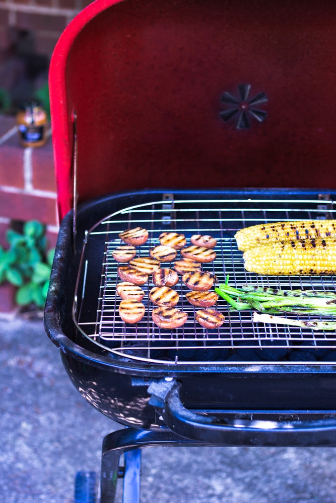 3/4 angled view of an outdoor grill with potatoes, corn and scallions on top. The grill has a red lid.