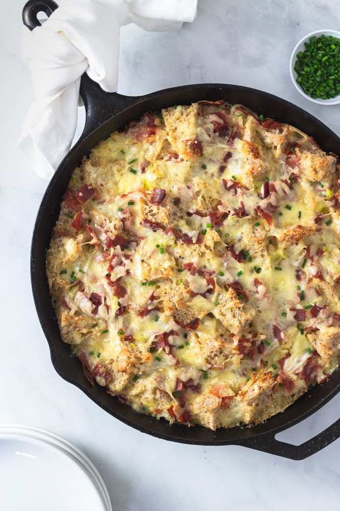 Overhead shot of a Ham and Cheese Strata made with Bayonne Ham in a cast iron pan on a marble surface surrounded by a bowl of chopped chives and a stack of white plates.