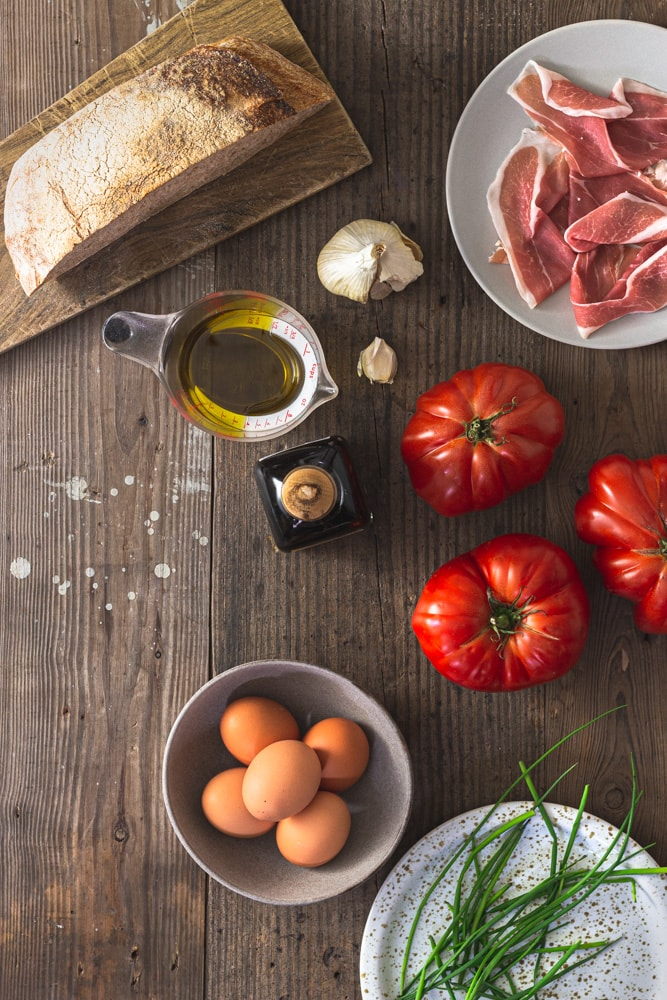 Overhead shot of ingredients for Salmorejo, a Spanish chilled tomato soup topped with hard cooked eggs and serrano ham. Ingredients include sour dough bread, ham, garlic, heirloom tomatoes, olive oil, sherry vinear, eggs and chives on a rustic grey wood surface.