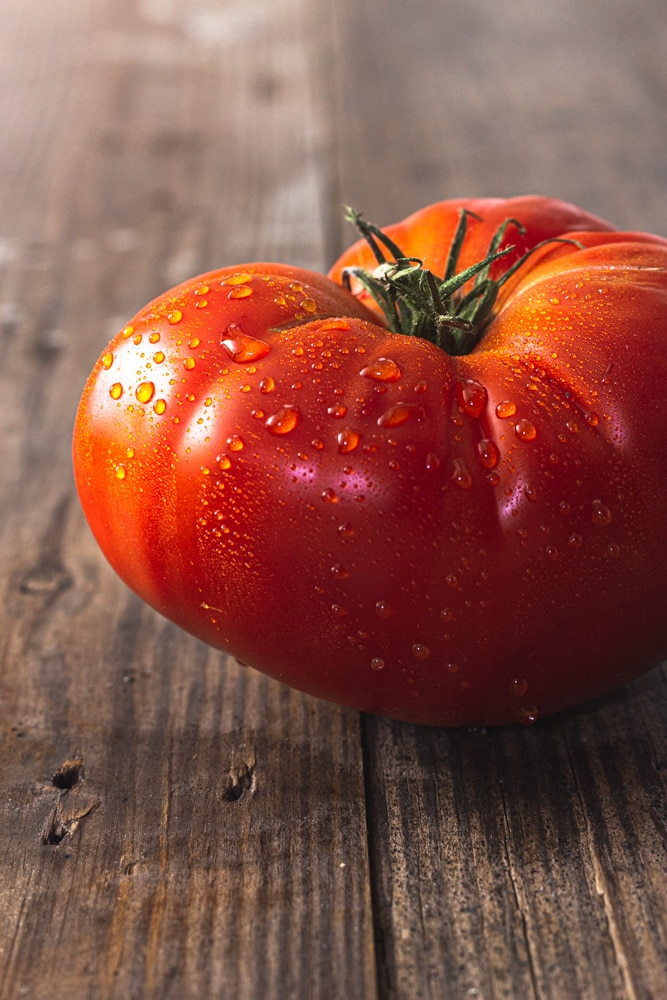 Straight on, close up shot of a large, red heirloom tomato with water droplets on it.