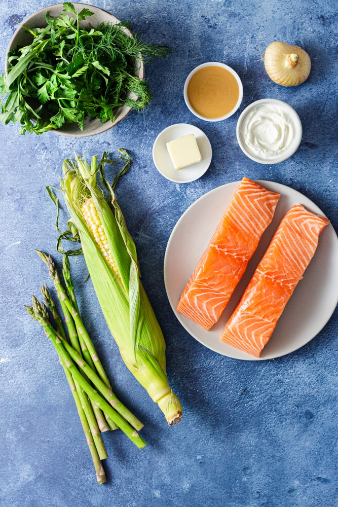 Overhead shot of ingredients for miso butter salmon, including fresh salmon, butter, white miso, a cipollini onion, yogurt, corn, asparagus and mixed herbs on a blue textured surface.