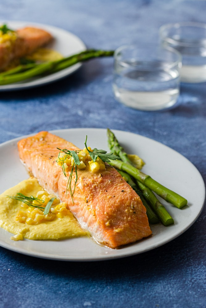 Angled shot of two plates of miso butter salmon over corn puree topped with whole corn and mixed herbs, and served with asparagus. The plates are surrounded by gold utensils and water glasses on a blue textured surface.