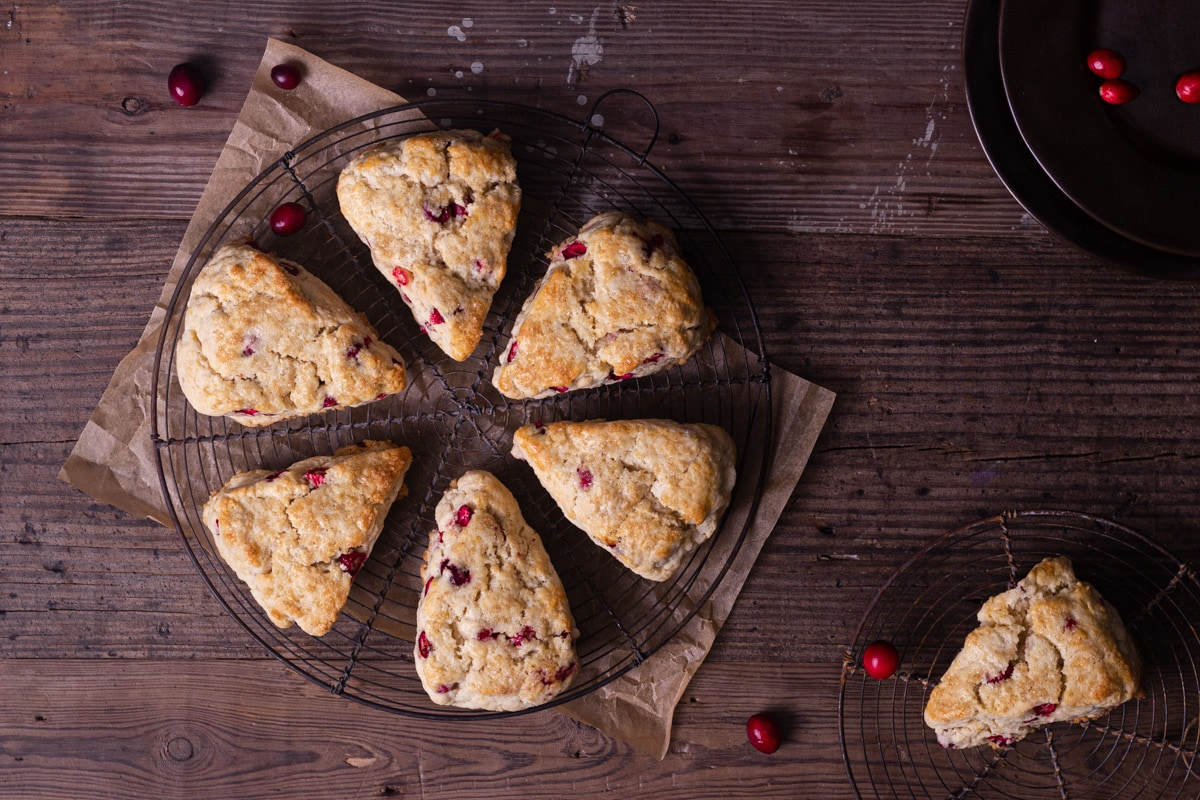 Overhead shot of Cranberry Orange Scones on a round wire rack on a rustic wood surface with a few fresh cranberries scattered around.
