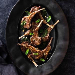 Lamb Chops with Mint Pesto on a black platter and dark grey surface.