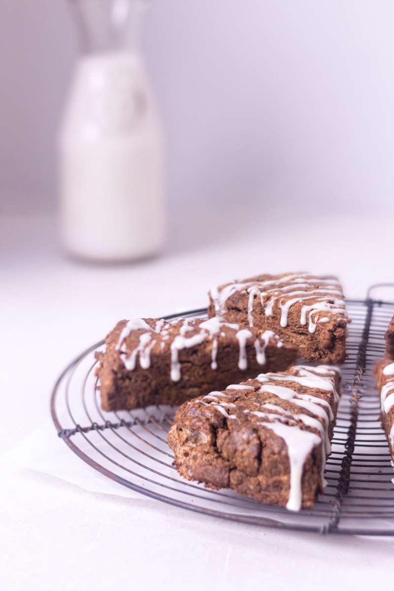 Straight on shot of gingerbread scones with lemon glaze on a round baking rack with a cream colored background and jug of milk.