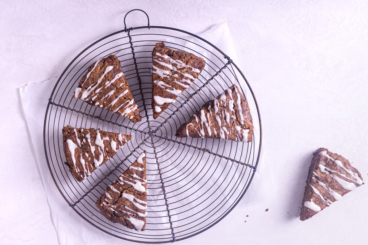 Overhead shot of gingerbread scones with lemon glaze on a round baking rack with a cream colored background.