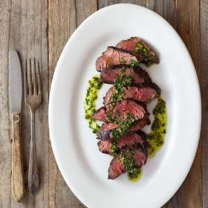 Hanger Steak with Salsa Verde sliced on a white plate on a wood surface.