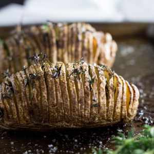 Close up of Hasselback Potatoes topped with thyme on a baking sheet.