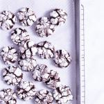 Overhead shot of Chocolate Crinkle Cookies scattered on a parchment lined baking sheet with a marble surface.