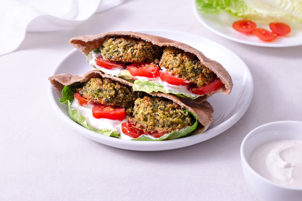 Straight on view of a crispy, baked falafel sandwich with lettuce, tomato and tahini yogurt sauce on a white plate surrounded by the sandwich ingredients and a dish towel on an off white surface.