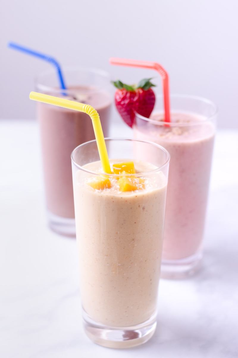 Three breakfast oatmeal smoothies : turmeric coconut mango in front, and  strawberry banana and chocolate peanut butter smoothies angled behind.