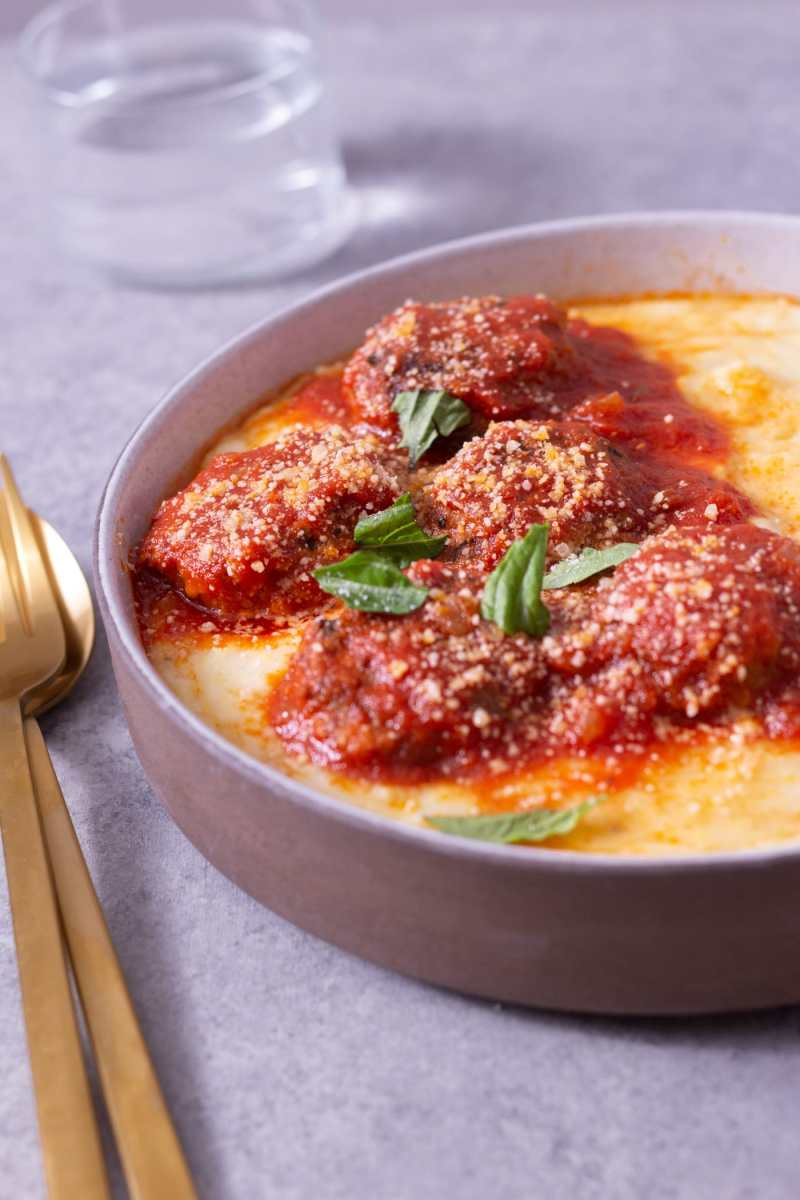 Close up angled view of a bowl of polenta topped with Instant Pot Meatballs in tomato sauce next to gold utensils on a light grey surface.