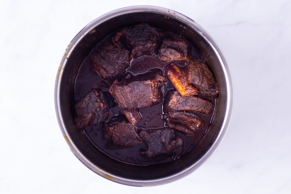 Braised short ribs with red wine tomato broth in a metal bowl.