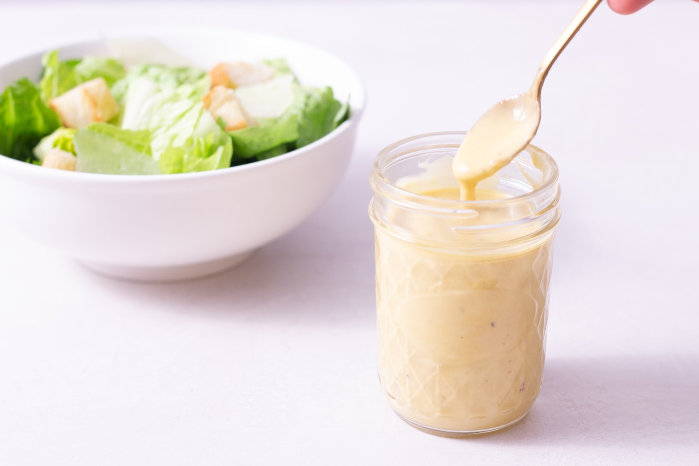 Straight on shot of a jar of Caesar Dressing with a spoon in it with Caesar Salad in the background.