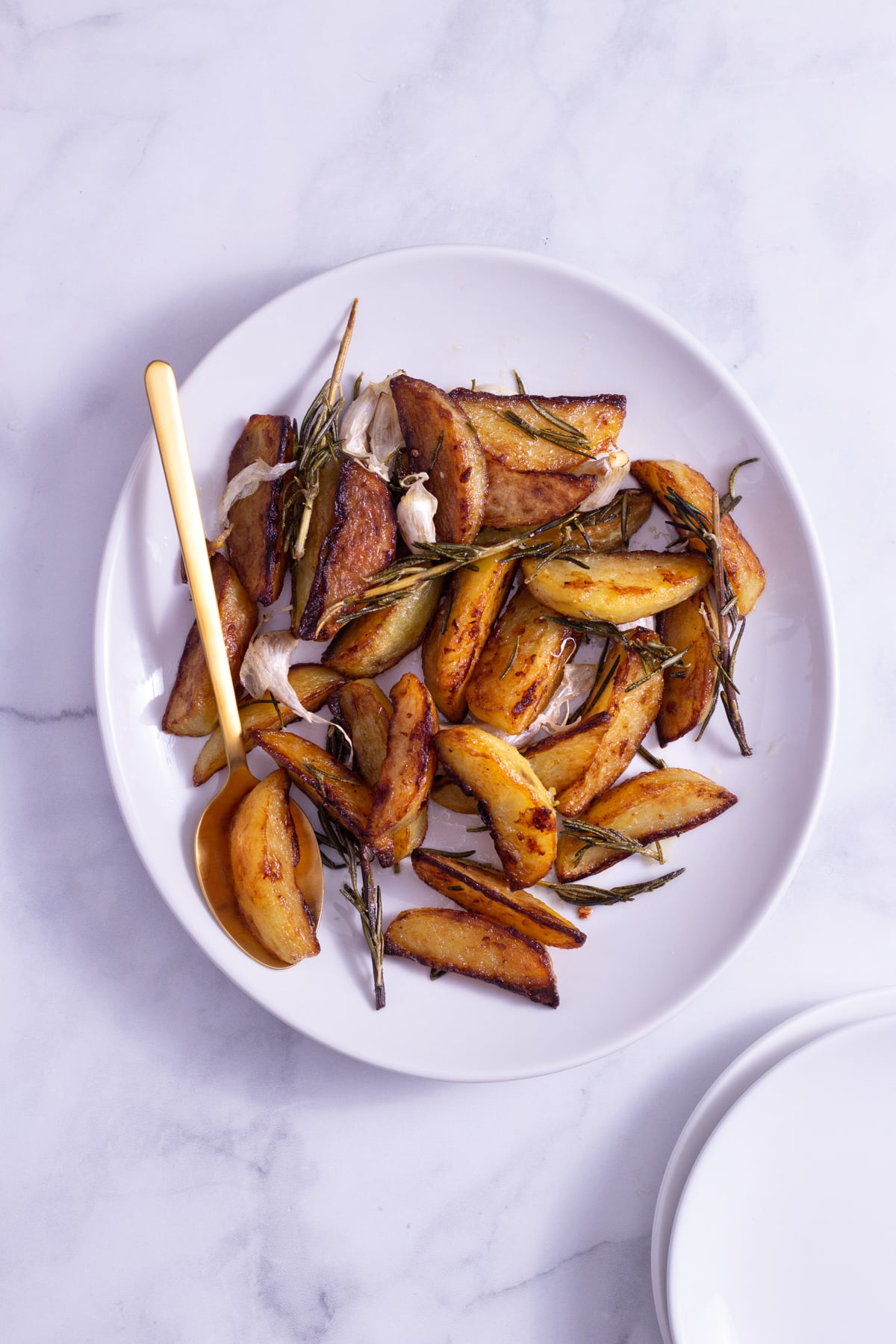Overhead view of potato wedges with fresh rosemary and garlic cloves on a white platter with a gold spoon on a marble surface.