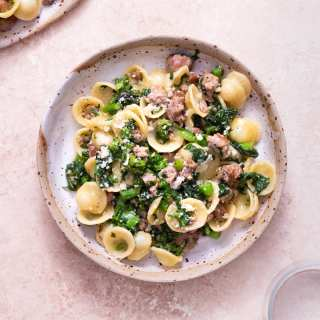 Overhead view of a bowl of Pasta with Sausage and Broccoli Rabe surrounded by a plate of pasta and two glasses on a light brown, textured surface.