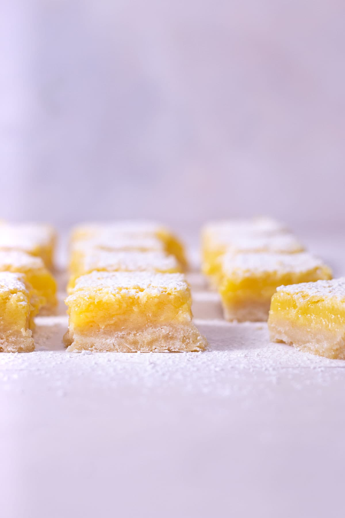 Straight on view of Lemon Bars lined up in a grid with a light blue background.