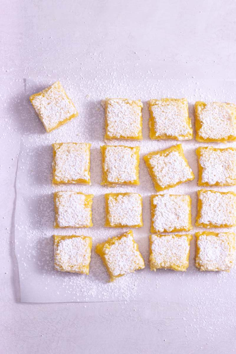 Overhead view of lemon squares on parchment on a light surface.
