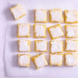Overhead view of lemon bars on parchment on a light surface.
